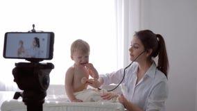 El estudiar en línea, mujer del doctor con los controles del estetoscopio al latido del corazón y respiración del muchacho gritad almacen de video