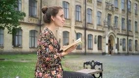 El estudiar femenino hermoso joven del estudiante universitario, libro de lectura y sentada en banco en la calle cerca de la univ almacen de metraje de vídeo