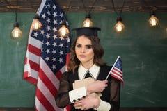 El estudiar inglés habla Estudiantes universitarios en biblioteca contra la imagen compuesta de la bandera nacional de los E.E.U. Imagen de archivo libre de regalías