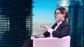El estudio de la TV Primer de la morenita en vidrios Ella se sienta en el estudio en un traje de negocios y da entrevistas almacen de metraje de vídeo