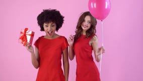 El estudio de las mujeres jovenes aislado en día rosado del ` s de las mujeres en rojo se viste con el regalo y el globo almacen de video