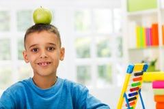 El estudio del niño y tiene manzana en cabeza Imagenes de archivo