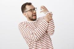 El estudio tiró de hombre adulto infantil divertido con la cerda en vidrios, intentando celebrar el ataque de la mano, celebrando Foto de archivo