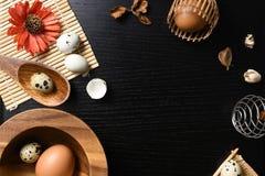 El estudio tiró de huevos en un fondo de madera negro Fotografía de archivo