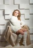 El estudio tiró de mujer atractiva en calcetines y del suéter que presentaba en silla Foto de archivo