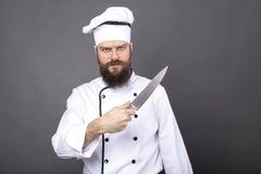 El estudio tiró de un cocinero barbudo que sostenía un cuchillo afilado grande fotos de archivo libres de regalías