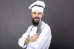 El estudio tiró de un cocinero barbudo que sostenía un cuchillo afilado grande fotografía de archivo libre de regalías