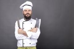El estudio tiró de un cocinero joven barbudo feliz que sostenía los cuchillos afilados foto de archivo libre de regalías