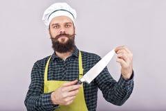 El estudio tiró de un hombre barbudo que sostenía un cuchillo afilado grande fotografía de archivo