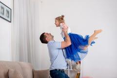 El estudio tiró de un padre que levantaba cariñosamente a la pequeña hija para arriba fotografía de archivo libre de regalías