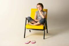 El estudio tiró de una chica joven que se sentaba en silla amarilla Foto de archivo libre de regalías