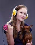 El estudio tiró de una muchacha adolescente sonriente con los auriculares y el perrito Fotos de archivo