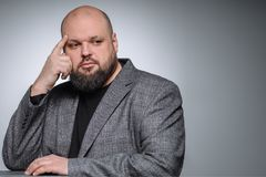 El estudio tiró del hombre de negocios gordo que pensaba contra fondo gris Hombre adulto lindo en un traje gris Fotografía de archivo