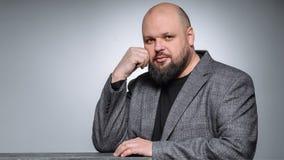 El estudio tiró del hombre de negocios gordo que pensaba contra fondo gris Hombre adulto lindo en un traje gris Imagenes de archivo
