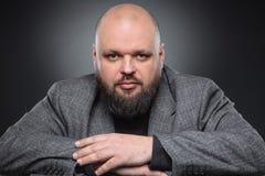El estudio tiró del hombre de negocios gordo que pensaba contra fondo gris Hombre adulto lindo en un traje gris Fotos de archivo libres de regalías