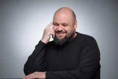 El estudio tiró del hombre de negocios gordo que sonreía contra fondo gris Hombre adulto lindo en golf negro Retrato expresivo Fotografía de archivo