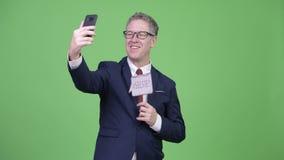 El estudio tiró del hombre de negocios maduro feliz que tomaba el selfie con la muestra de papel metrajes