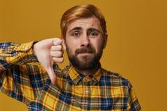 El estudio tirado de varón elegante, barbudo con el pelo rubio teñido del oro muestra la muestra de la aversión Expresión y desap Fotografía de archivo