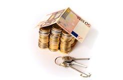 El euro acuña la casa de la pila con el tejado y la llave del billete de banco Fotografía de archivo libre de regalías