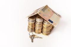 El euro acuña la casa de la pila con el tejado y la llave del billete de banco Imagenes de archivo