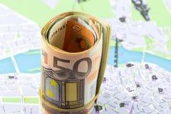El euro cincuenta rodó para arriba en un mapa como fondo Imagenes de archivo