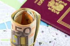 El euro cincuenta rodó para arriba en un mapa como un fondo y pasaporte español Fotografía de archivo libre de regalías