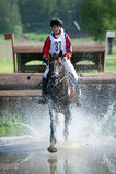 El eventer de la mujer en caballo se corre en salto de agua Fotografía de archivo