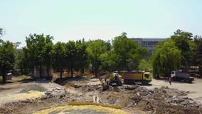 El excavador amarillo cava la tierra del hoyo de la fundación y cargo de la dirección con un cubo al camión Preparación de la bas almacen de video