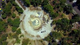 El excavador amarillo cava la tierra del hoyo de la fundación y cargo de la dirección con un cubo al camión Preparación de la bas metrajes