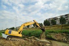El excavador amarillo excava en la ciudad del districto Imágenes de archivo libres de regalías