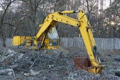 El excavador amarillo viejo con un cubo oxidado se coloca afuera en la vegetación seca Imagenes de archivo