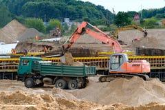 El excavador carga la tierra en el camión Fotos de archivo