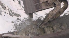 El excavador carga las piedras en los coches metrajes