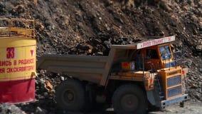 El excavador carga una piedra en el camión pesado en el granito de la explotación minera de la mina almacen de metraje de vídeo