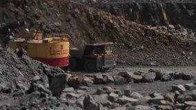 El excavador carga una piedra en el camión pesado en el granito de la explotación minera de la mina almacen de video