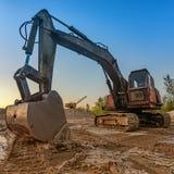 El excavador con un cubo grande extrae la arena en una mina Fotos de archivo libres de regalías