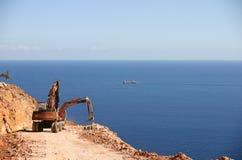 El excavador construye el camino Imagen de archivo