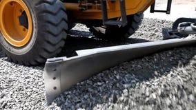 El excavador del graduador separó la piedra machacada en el camino almacen de metraje de vídeo