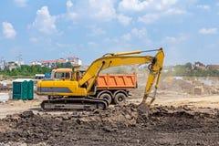 El excavador está funcionando en emplazamiento de la obra Caterpillar en la acción Fotos de archivo libres de regalías
