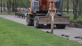 El excavador extrae el encintado del camino almacen de metraje de vídeo