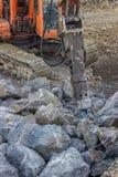 El excavador montó el martillo perforador hidráulico usado para romper para arriba el hormigón Imágenes de archivo libres de regalías