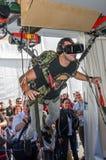 El experimentador del hombre siente el simulador de la instalación el saltar en caída libre de los vidrios con la realidad virtua Fotografía de archivo