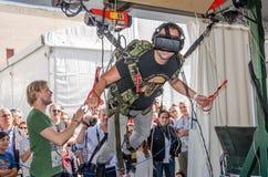 El experimentador del hombre siente el simulador de la instalación el saltar en caída libre de los vidrios con la realidad virtua Foto de archivo libre de regalías
