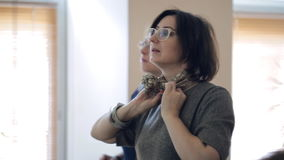 El experto de la moda muestra manera elegante y fácil de llevar un pañuelo para el cuello almacen de metraje de vídeo