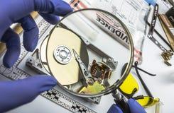 El experto de la polic?a examina con el disco duro de la lupa en busca de pruebas imagen de archivo