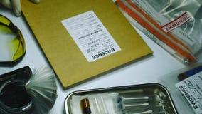 El experto de la policía examina las fotografías de las pruebas en caso de asesinato en el criminal del laboratorio metrajes