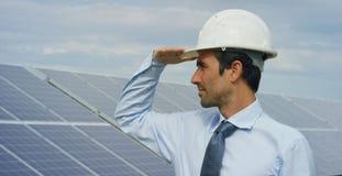 El experto del ingeniero en los paneles fotovoltaicos de energía solar con teledirigido realiza las acciones rutinarias para la s Foto de archivo libre de regalías