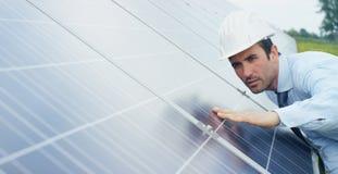 El experto del ingeniero en los paneles fotovoltaicos de energía solar con teledirigido realiza las acciones rutinarias para la s Fotos de archivo libres de regalías