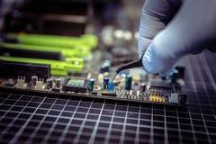 El experto está poniendo el puente eléctrico en contactos de la placa madre con los fórceps miniatura fotos de archivo