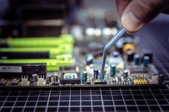 El experto está poniendo el puente eléctrico en contactos de la placa madre imagen de archivo libre de regalías